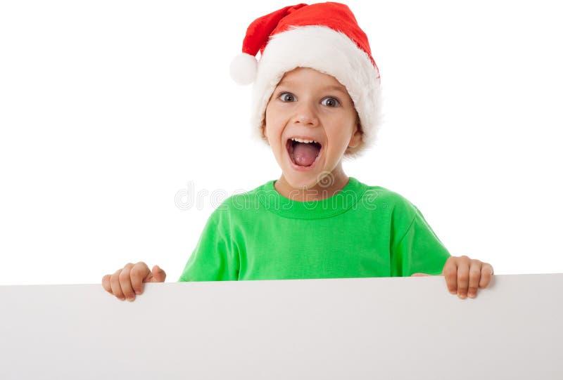 Muchacho de la Navidad que se coloca con el espacio en blanco vacío imagen de archivo