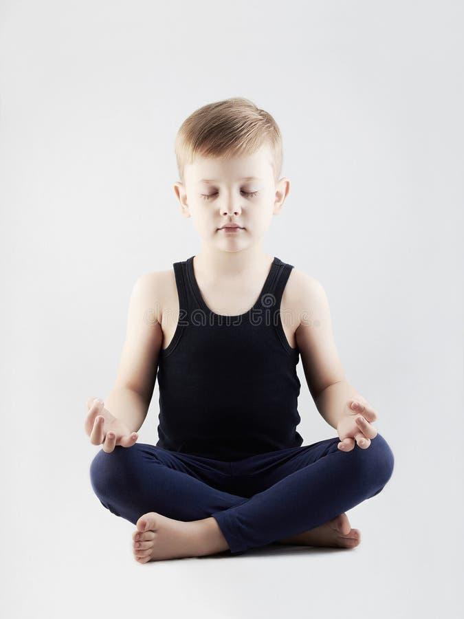 Muchacho de la yoga niño en la posición de loto meditación y relajación de los niños imagen de archivo libre de regalías