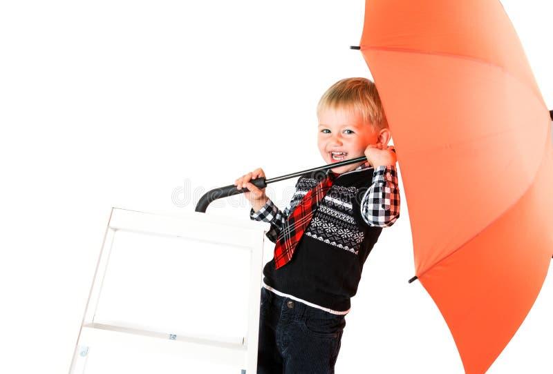 Muchacho de Loughing con el tiro del estudio del paraguas aislado en un backg blanco fotos de archivo