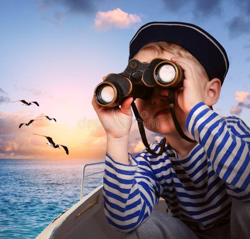 Muchacho de marinero con los prismáticos en el barco imagen de archivo libre de regalías