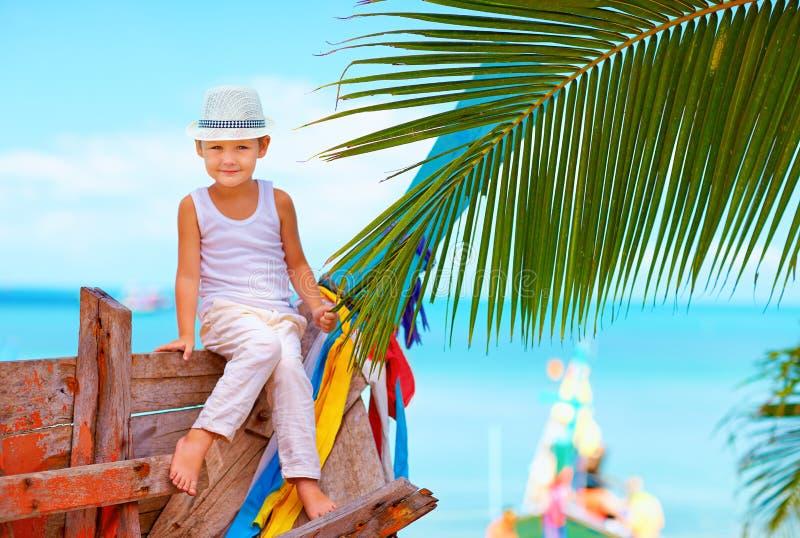 Muchacho de moda lindo que presenta en el barco viejo en la playa tropical imagen de archivo libre de regalías