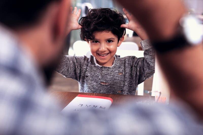 Muchacho de ojos oscuros sonriente lindo que lleva el suéter gris que juega trucos fotografía de archivo libre de regalías