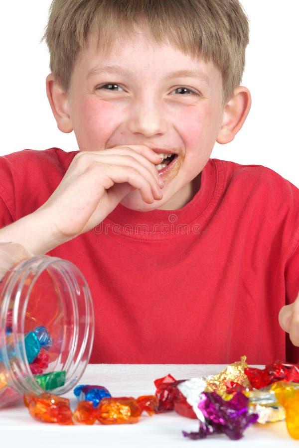 Muchacho de risa con el caramelo imagen de archivo