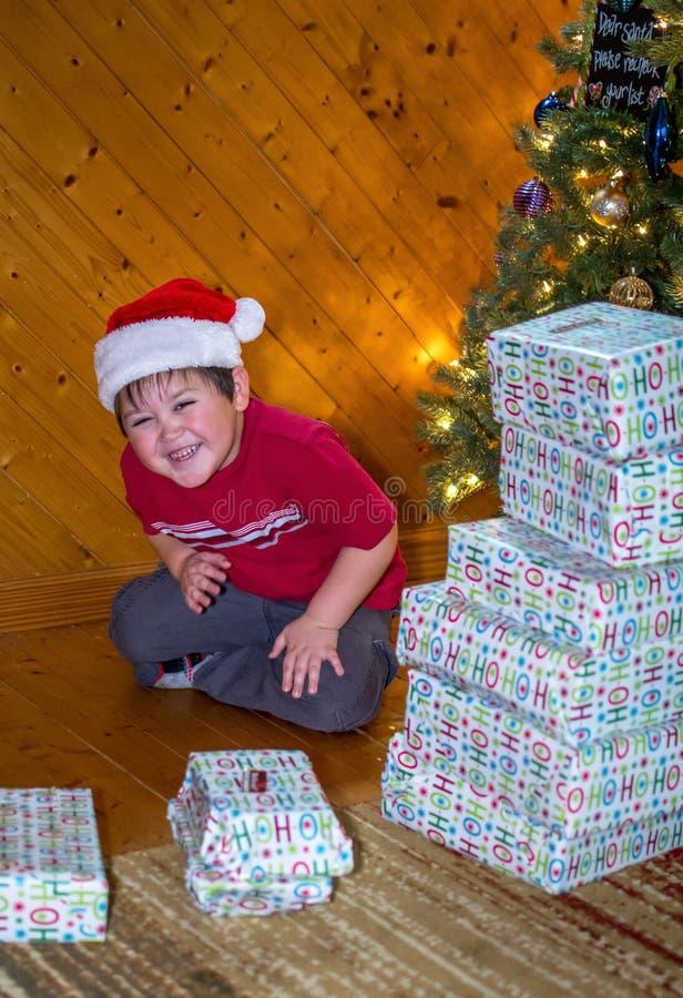 Muchacho de risa con la pila de regalos de Navidad fotos de archivo