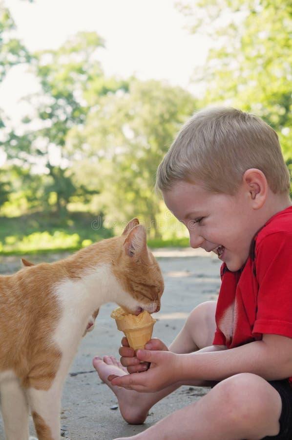 Muchacho de risa cosquilleado por el gato que come su helado foto de archivo libre de regalías