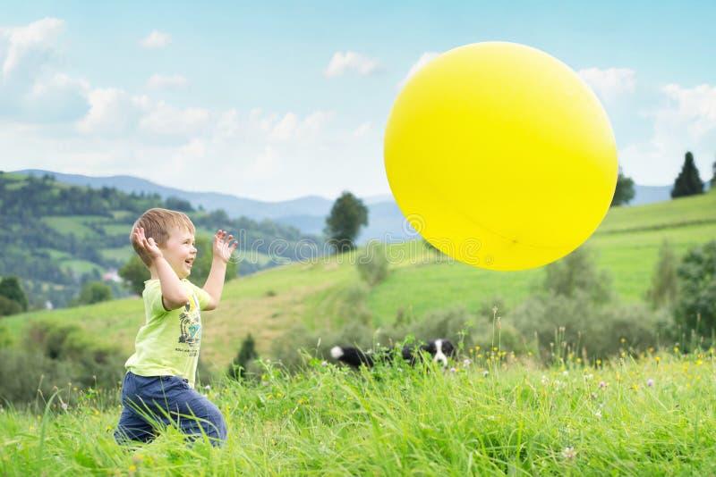 Muchacho de risa que persigue un globo imagenes de archivo