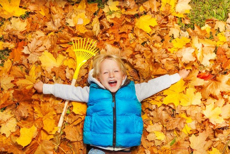 Muchacho de risa que pone en las hojas de otoño con el rastrillo imágenes de archivo libres de regalías