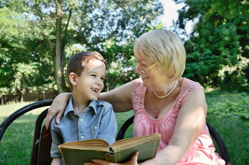 Muchacho de risa y su abuela que leen un libro en el parque imagenes de archivo