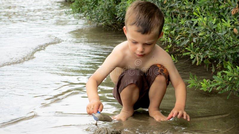 Muchacho de seis años que juega en la arena en el lago fotos de archivo libres de regalías