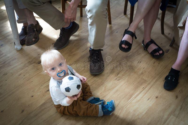 Muchacho de un año con la bola con adultos fotografía de archivo libre de regalías