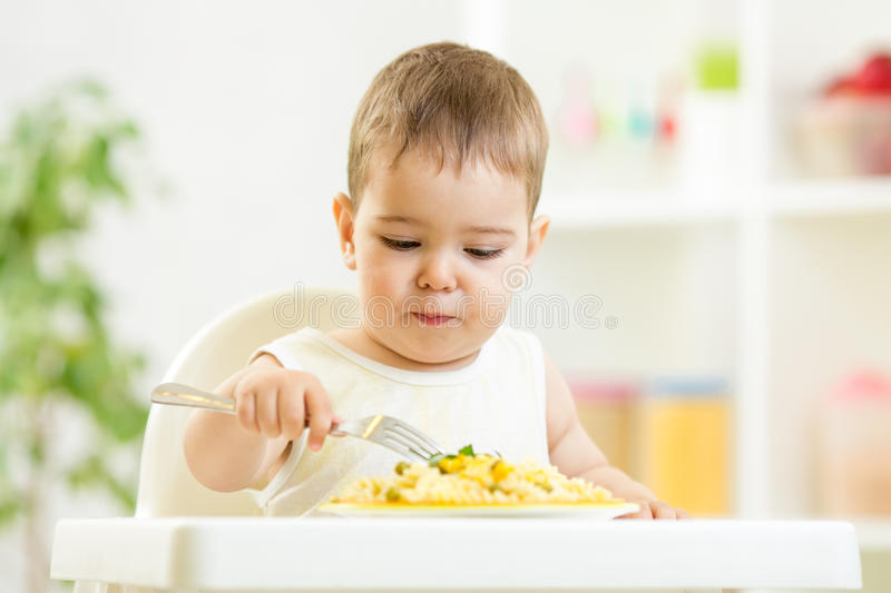 Muchacho de un año del niño en un highchair para alimentar imagen de archivo