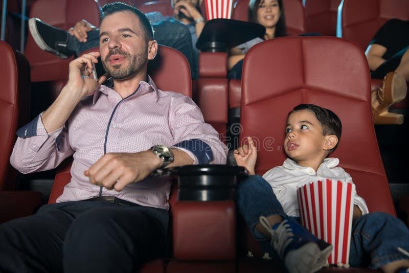 Muchacho decepcionado en las películas con el papá imagen de archivo