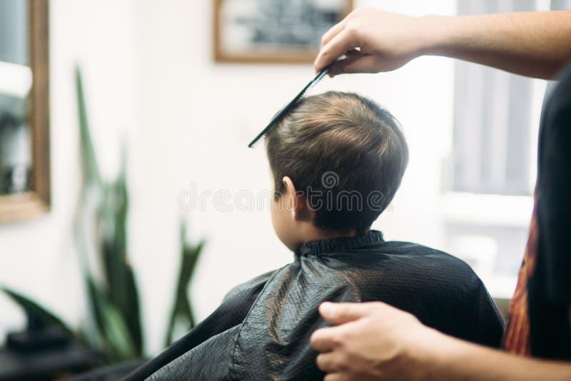muchacho del Little que consigue corte de pelo de Barber While Sitting In Chair en la barbería  foto de archivo libre de regalías