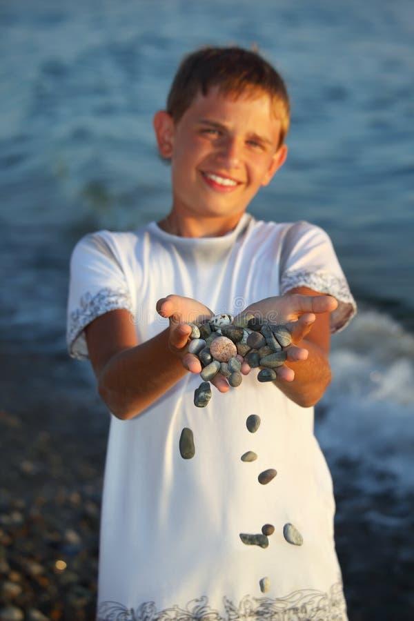 Muchacho del adolescente con el puñado de piedras en manos foto de archivo