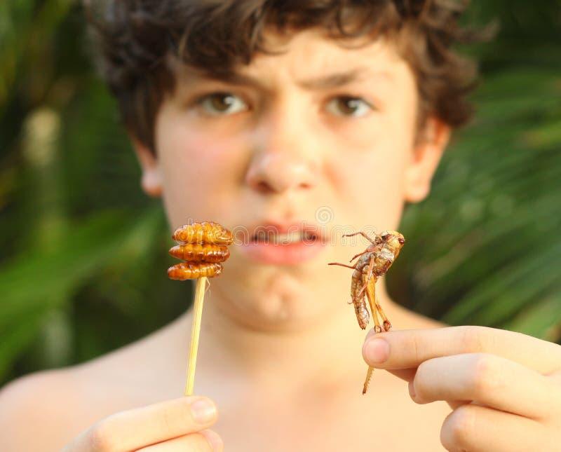 Muchacho del adolescente con la comida tailandesa extraña unusial del control de la mueca del repugnancia imagenes de archivo