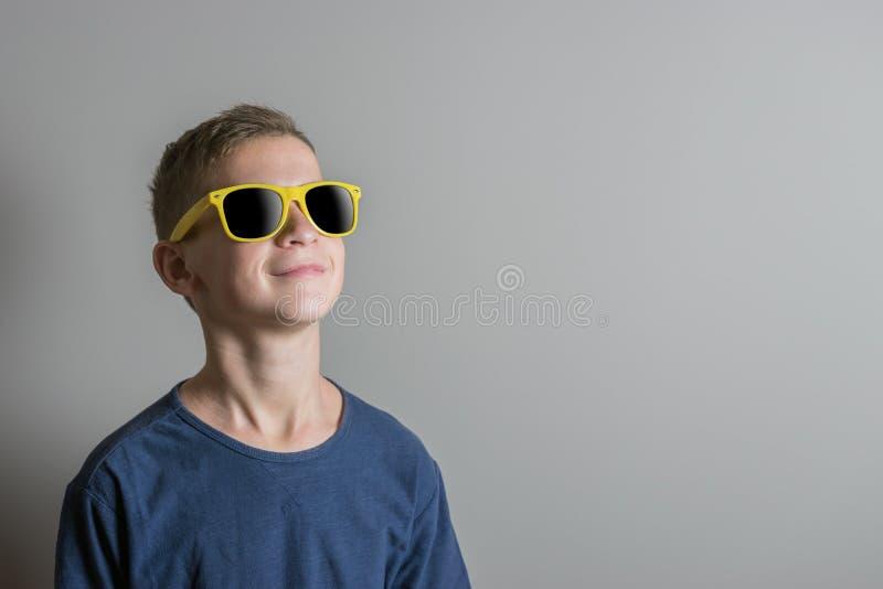 Muchacho del adolescente en gafas de sol y camiseta azul en fondo brillante fotos de archivo libres de regalías