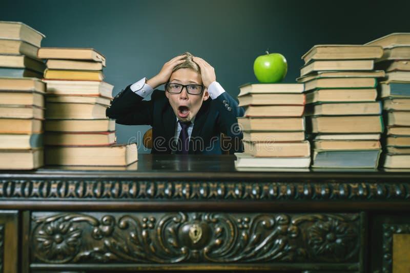 Muchacho del alumno en la tensión o la depresión en la sala de clase de la escuela imagenes de archivo