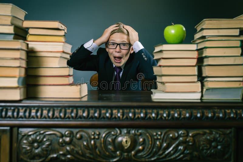 Muchacho del alumno en la tensión o la depresión en la sala de clase de la escuela imagen de archivo