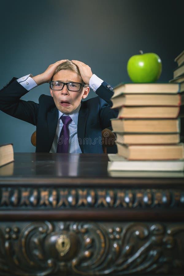 Muchacho del alumno en la tensión o la depresión en la sala de clase de la escuela fotos de archivo