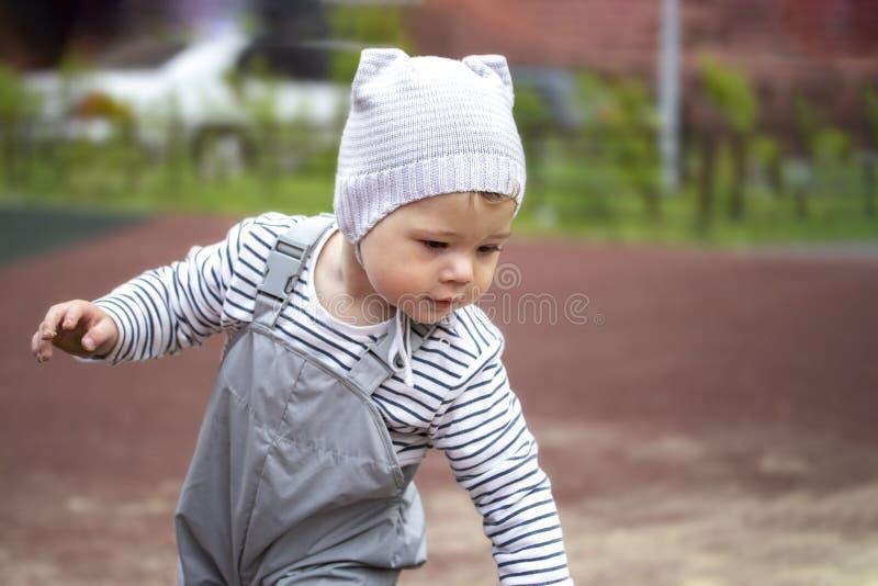Muchacho del bebé de 1 año en gris, sombrero y pantalones con las correas, para un paseo Retrato de un niño de 1 año foto de archivo