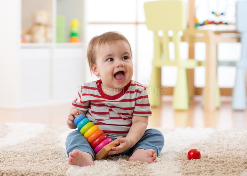 Muchacho del bebé que juega dentro con el juguete de desarrollo que se sienta en la alfombra suave foto de archivo libre de regalías