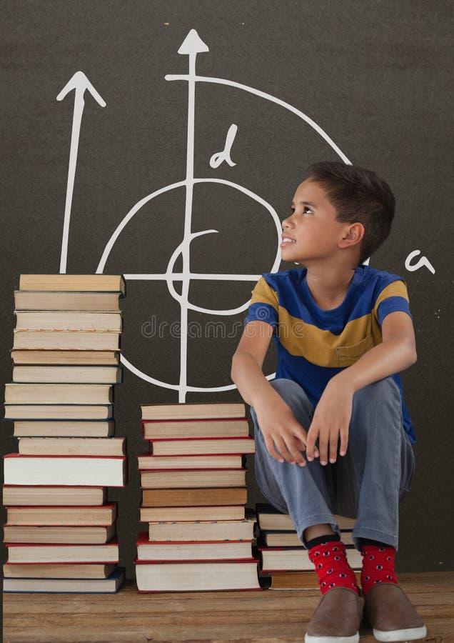 Muchacho del estudiante en una tabla que mira para arriba contra la pizarra gris con la escuela y el gráfico de la educación imagen de archivo