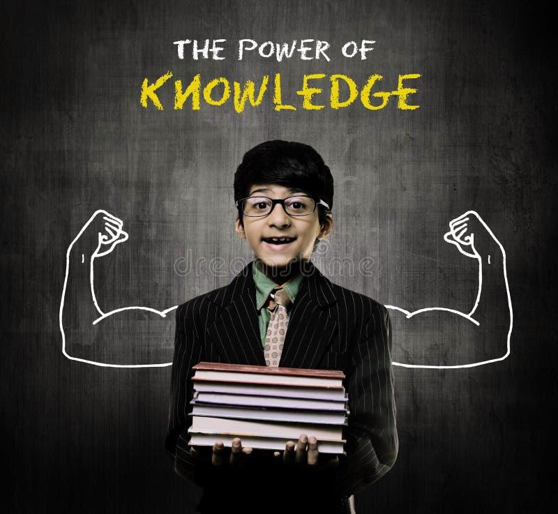 Muchacho del genio que sostiene los libros que llevan los vidrios, poder del conocimiento imagen de archivo libre de regalías