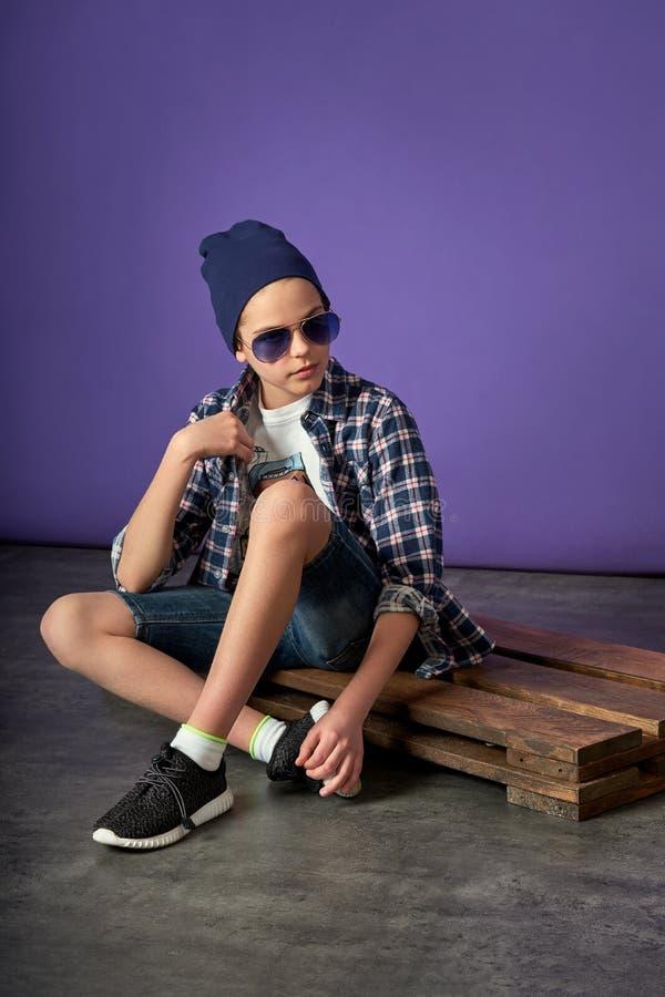 Muchacho del hombre de la moda de los jóvenes que se sienta en el piso imágenes de archivo libres de regalías