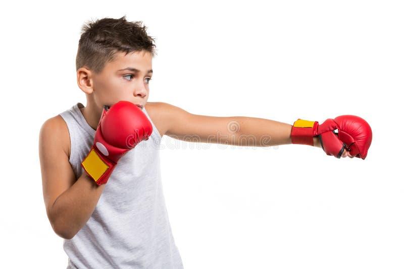 Muchacho del karate en la postura que lucha, huelgas con una mano, en sus guantes rojos de las manos, en un fondo blanco foto de archivo libre de regalías