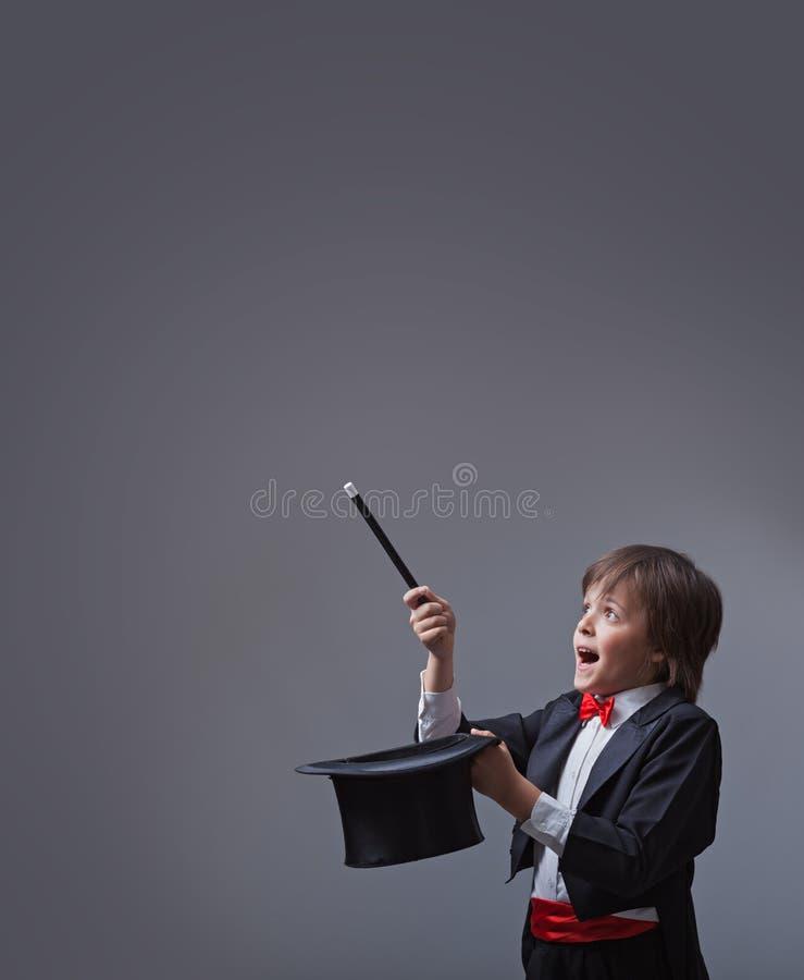 Muchacho del mago que se realiza con la vara y el casco mágicos fotografía de archivo libre de regalías