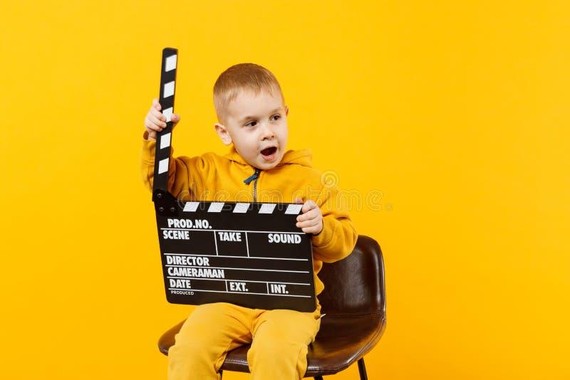 Muchacho del niño 3-4 años en la ropa amarilla aislada en el fondo anaranjado de la pared, retrato del estudio de los niños Gente imagen de archivo libre de regalías