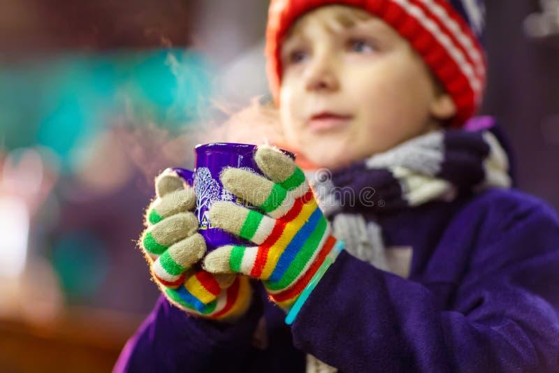 Muchacho del niño con el chocolate caliente en mercado de la Navidad foto de archivo