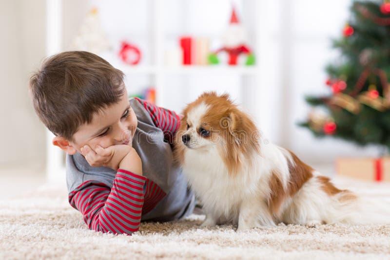 Muchacho del niño con el perro que miente en el árbol de navidad en el piso fotografía de archivo