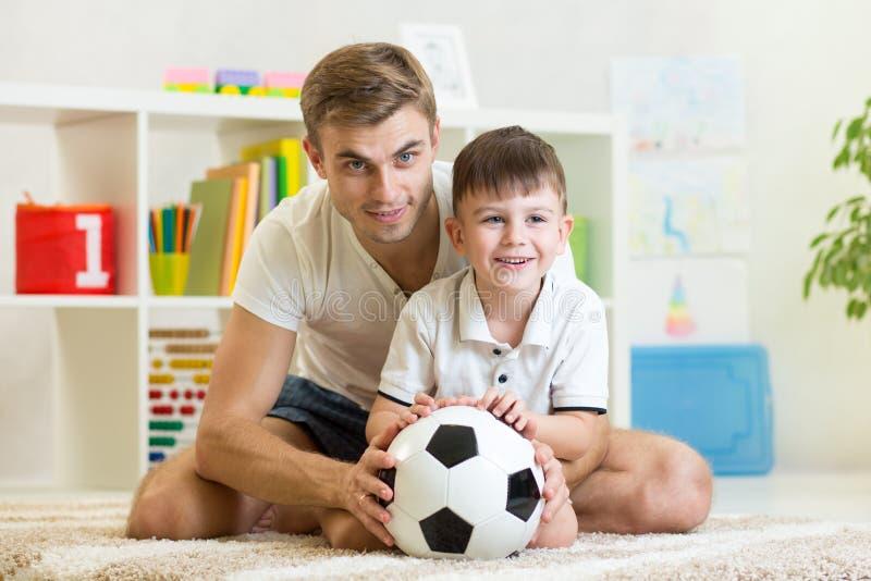 Muchacho del niño con la bola del pie del juego del papá en casa fotografía de archivo