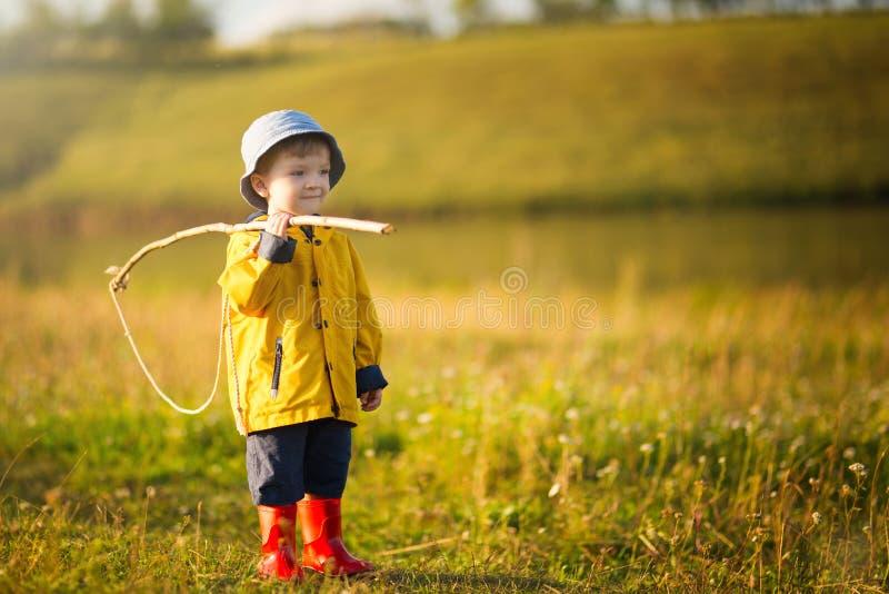 Muchacho del niño con la caña de pescar lista para pescar imagen de archivo libre de regalías