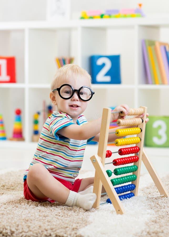 Muchacho del niño con las lentes que juegan el juguete del ábaco foto de archivo