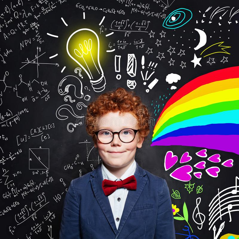 Muchacho del niño con los vidrios que llevan del pelo del jengibre en fondo de la pizarra con fórmulas de la ciencia, el modelo d foto de archivo libre de regalías
