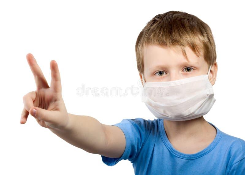 Muchacho del niño de la enfermedad de la gripe en máscara quirúrgica imagenes de archivo