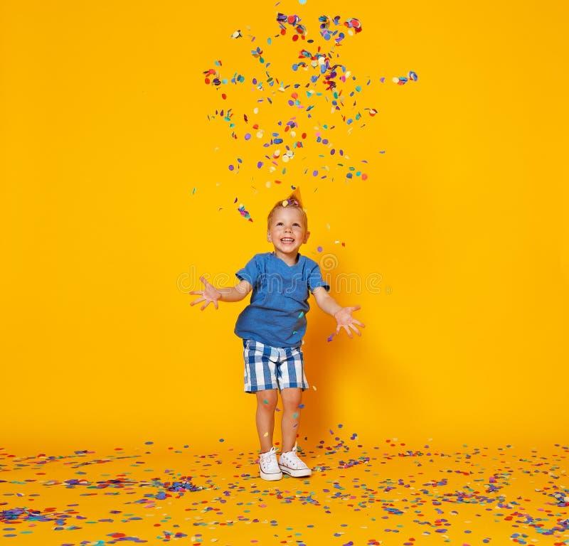 Muchacho del niño del feliz cumpleaños con confeti en fondo amarillo fotos de archivo libres de regalías