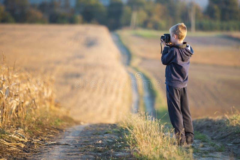Muchacho del niño joven con la cámara de la foto que toma la imagen del campo de trigo en fondo rural borroso fotos de archivo libres de regalías