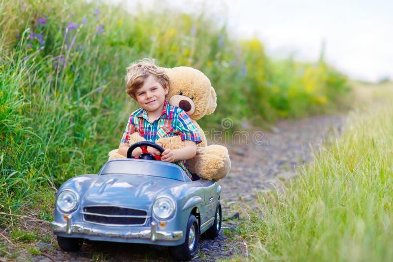 Muchacho del niño que conduce el coche grande del juguete con un oso, al aire libre foto de archivo libre de regalías