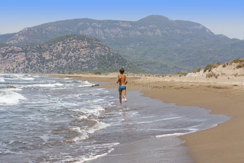 Muchacho del niño que corre en la foto de la playa imágenes de archivo libres de regalías