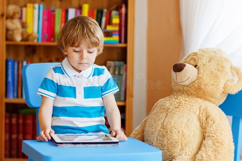 Muchacho del niño que juega con la tableta en su sitio en casa fotografía de archivo