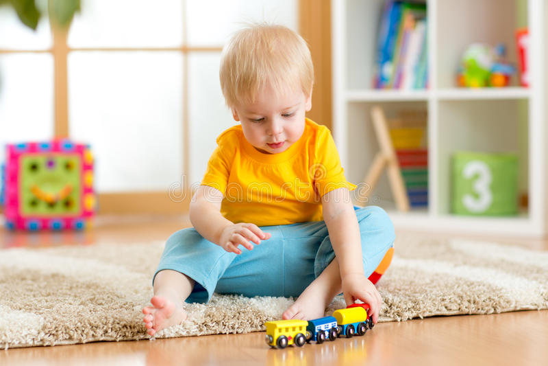 Muchacho del niño que juega con los juguetes dentro en casa o guardería fotos de archivo