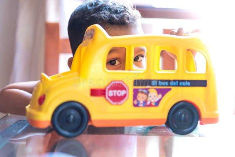 Muchacho del niño que juega con un juguete del autobús escolar dentro imagen de archivo libre de regalías