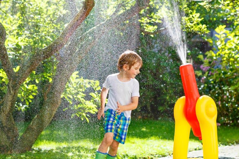 Muchacho del niño que juega con una manguera y un agua de jardín fotografía de archivo