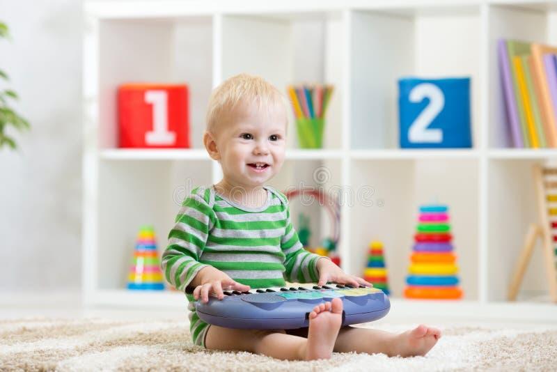 Muchacho del niño que juega el piano del juguete en cuarto de niños fotografía de archivo libre de regalías