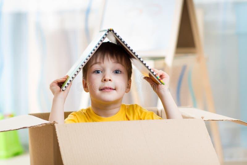 Muchacho del niño que juega en una casa del juguete imagen de archivo
