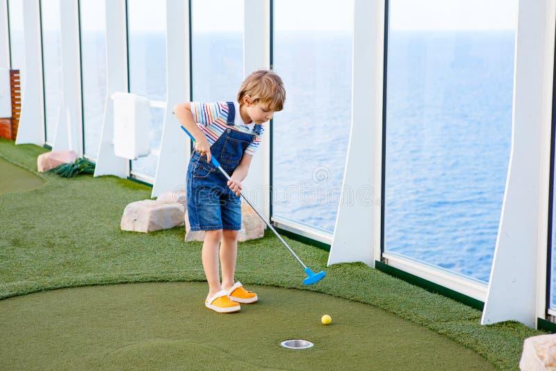 Muchacho del niño que juega a mini golf en un trazador de líneas de la travesía imagen de archivo