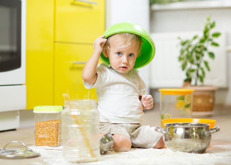 Muchacho del niño que se sienta en el piso de la cocina y que juega con la harina fotografía de archivo libre de regalías